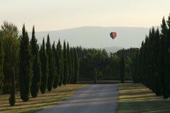 Steigen Sie das Fliegen über die Provençal-cypres nahe Lacoste im VA im Ballon auf lizenzfreie stockbilder