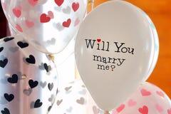 Steigen Sie mit einer Aufschrift, Sie heiratet mich für Heiratsrecep im Ballon auf Stockfoto