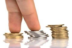 Steigende Finger auf dem Diagramm gebildet von den Münzen Lizenzfreies Stockfoto