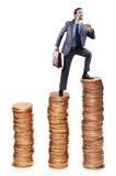 Steigende Goldmünzen des Geschäftsmannes Stockbilder