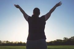 Steigende Hände der überladenen Frau in Richtung zum Himmel stockfoto