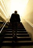 Steigende Treppen des alten Mannes in die Leuchte Lizenzfreie Stockfotografie