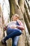 Steigender Baum des blonden Mädchens Stockfotos