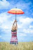 Steigender Regenschirm und Stellung des blonden Mädchens in Goldenem Lizenzfreies Stockfoto