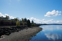 Steilacoom Washington. A railroad cargo train passes a section of rocky beach in Steilacoom, Washington with blue ocean water and blue cloudy sky royalty free stock photo