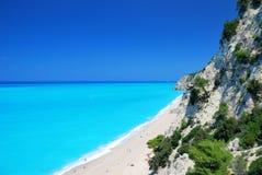 Steile Klippen und großer Strand mit blauem Meer Stockbilder