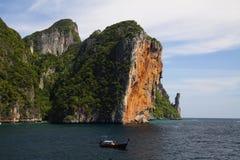 Steile rote Felsenwand, die vom Wasser in blauen Himmel von Tropeninsel Ko Phi Phi, Andaman-Meer, Thailand steigt lizenzfreie stockfotografie