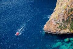 Steile Seeklippen und -boot im blauen Grottenbereich Stockbild