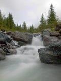Steiles steiniges Strombett des alpinen Baches Unscharfe Wellen des Stromes laufend über Flusssteine und Steine, Hochwasserniveau Stockfotografie