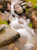 Steiles steiniges Strombett des alpinen Baches Unscharfe Wellen des Stromes laufend über Flusssteine und Steine, Hochwasserniveau Lizenzfreie Stockbilder