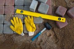 Stein blockiert Gummihammerniveauhandschuhe und -Maßband Stockbilder