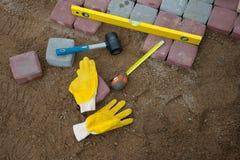 Stein blockiert Gummihammerniveauhandschuhe und -Maßband Stockfoto