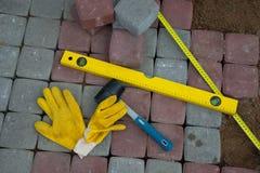 Stein blockiert Gummihammerniveauhandschuhe und -Maßband Stockbild