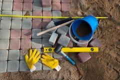 Stein blockiert Gummihammerniveauhandschuhe und -Maßband Stockfotos