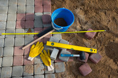 Stein blockiert Gummihammerniveauhandschuhe und -Maßband Stockfotografie