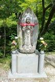Stein-Buddha mit den Händen umklammert auf Lotos Stockfotos