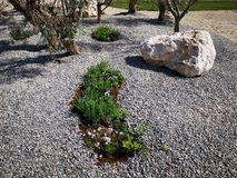 Stein dekorativ auf Kies und Grünfläche lizenzfreies stockbild