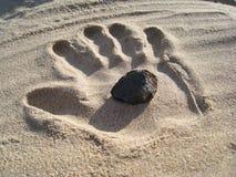 Stein in der Sand-Hand Lizenzfreie Stockfotografie