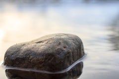 Stein in einem Fluss Stockbild