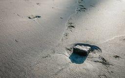 Stein in einem Grübchen auf dem Strand lizenzfreie stockbilder
