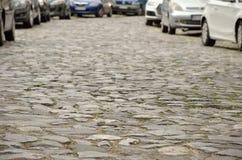 Stein gepflasterte Straße und Autos Stockbild