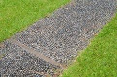 Stein gepflasterter Gehweg mit grünem Gras Lizenzfreie Stockfotos