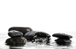 Stein im Wasser mit Tropfen Lizenzfreie Stockfotos