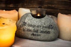Stein mit christlicher Schrift mit heller Kerze lizenzfreie stockfotos