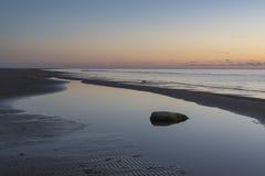 Stein und Küstenlinie bei Sonnenuntergang stockfoto