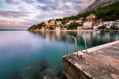 Steinanlegestelle im kleinen Dorf nahe Omis an der Dämmerung, Dalmatien Stockfoto