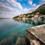 Steinanlegestelle im kleinen Dorf nahe Omis an der Dämmerung, Dalmatien Lizenzfreies Stockfoto