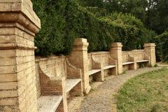 Steinbänke in einem Park. grüner Busch lizenzfreies stockbild