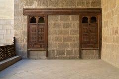Steinbacksteinmauer mit zwei eingebetteten verzierten hölzernen Schränken Lizenzfreie Stockbilder