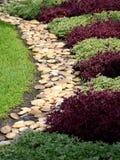 Steinbahn, die in Garten überschreitet Stockfotografie
