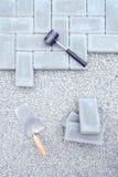 Steinblöcke für die Pflasterung des Niederlegungshintergrundes mit Hammer und Kelle Stockfotografie