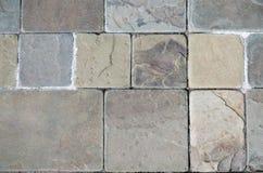 Steinboden in den warmen Farben Hintergrund von Steinziegelsteinen von verschiedenen Größen Stockfoto