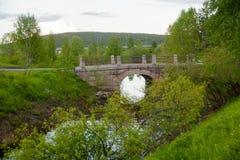 Steinbrücke über Fluss im Park im Sommer, Rovaniemi, Lappland-Region, Finnland Stockfotografie