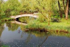 Steinbrücke über Fluss oder See in der Landschaft, stürmischer Himmel Stockbilder