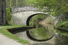 Steinbrücke über Kanal mit Ente und Reflexionen Lizenzfreies Stockbild