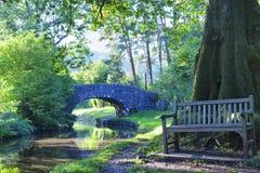 Steinbrücke, Bank durch Eiche durch englischen Kanal in einem Wald Stockfotos