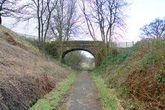 Steinbrücke, die einen Landweg kreuzt Lizenzfreie Stockbilder
