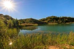 Steinbruch oder See oder Teich mit sandigem Strand, grünes Wasser, Bäume und Stockfoto