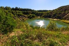 Steinbruch oder See oder Teich mit sandigem Strand, grünes Wasser, Bäume und Stockbild
