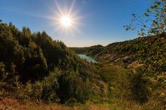 Steinbruch oder See oder Teich mit sandigem Strand, grünes Wasser, Bäume und Lizenzfreie Stockbilder