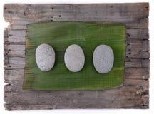Steine auf Bananenblatt mit hölzernem Hintergrund Stockbild