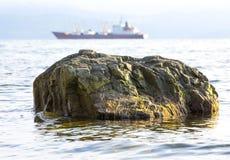 Steine auf dem Meer und Schiffe auf dem Hintergrund Lizenzfreie Stockfotografie