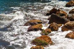 Steine auf dem Strand, über den die Wellen schlagen lizenzfreies stockfoto