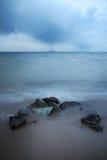 Steine auf der Bank des Sees im Blau des wolkigen Wetters Lizenzfreies Stockbild