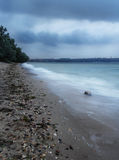 Steine auf der Bank des Sees im Blau des wolkigen Wetters Lizenzfreie Stockbilder