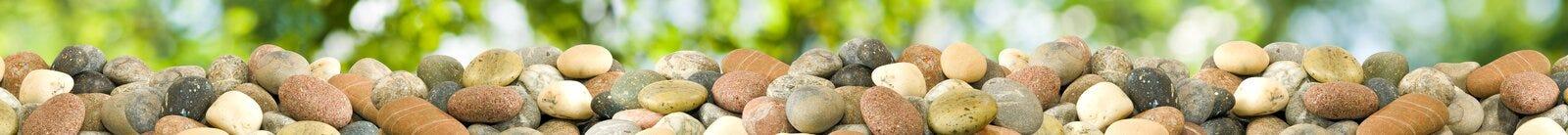 Steine auf einem grünen Hintergrund Panorama Lizenzfreie Stockbilder